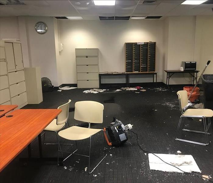 Office with wet floor with ceiling debris and filing cabinets